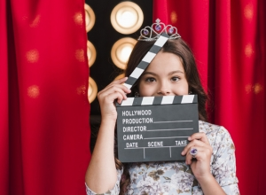 portrait-of-girl-wearing-crown-holding-clapper-board-in-front-of-her-face_23-2147883000